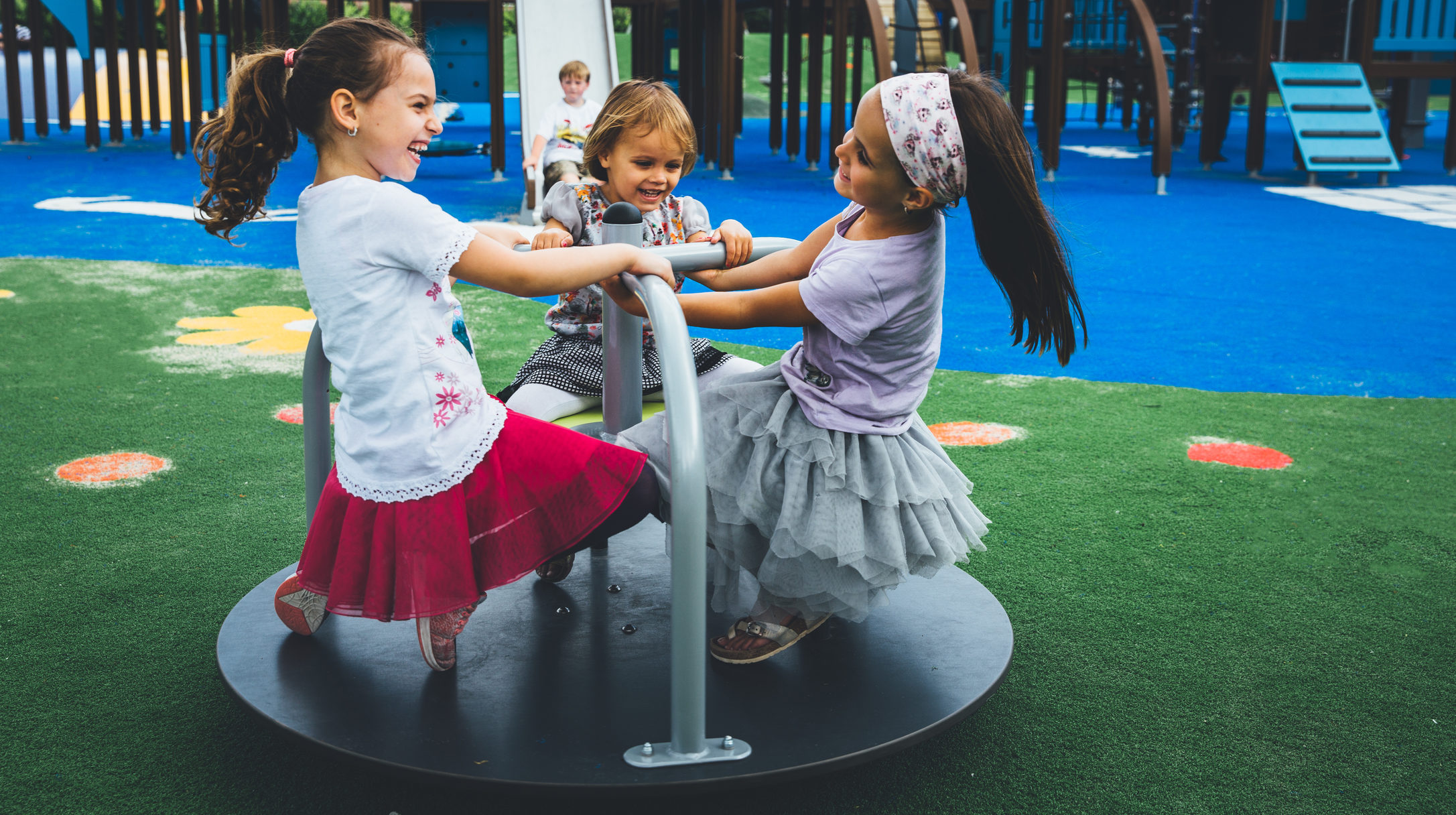 playground roundabout with 3 children playing