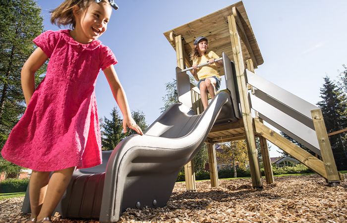 Children playing on slide outdoors