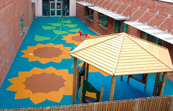 playground flooring safety surface installed in a court yard with flower graphics