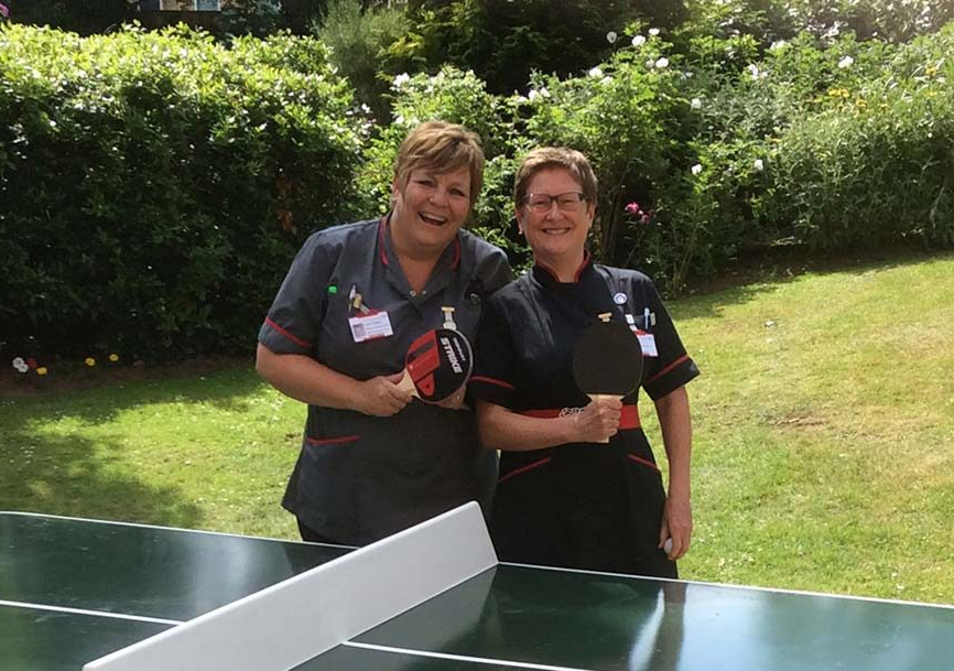 2 ladies standing at a table tennis table with bats